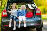 Little sisters sitting in a car just before leaving for a car vacation with their parents-family